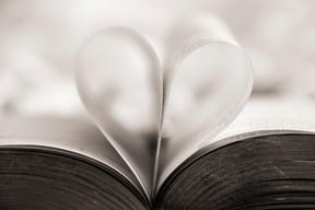 close up of book pages forming a heart