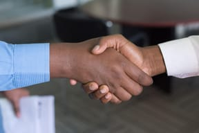 Two men shaking hands leading with love in the workplace