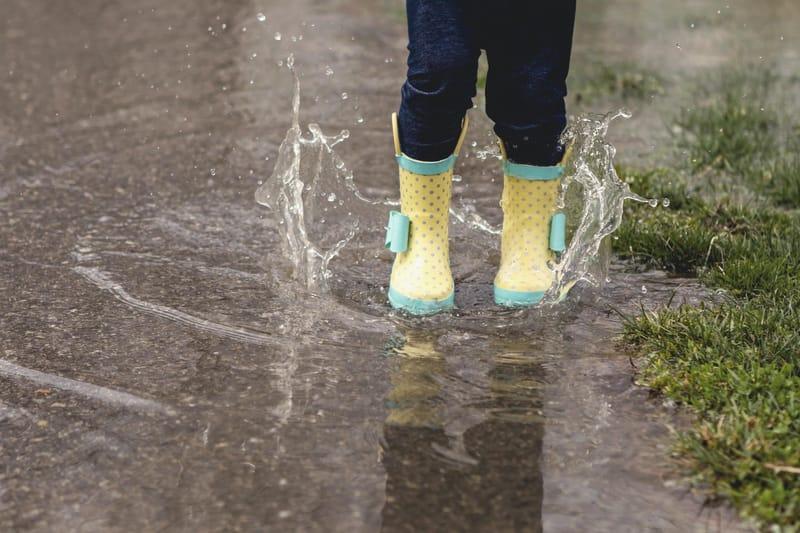 Child splashing in puddle wearing rainboots